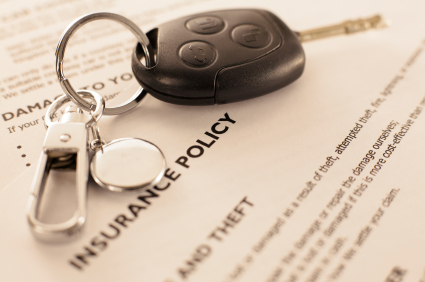 insurance policy papers with car key on top
